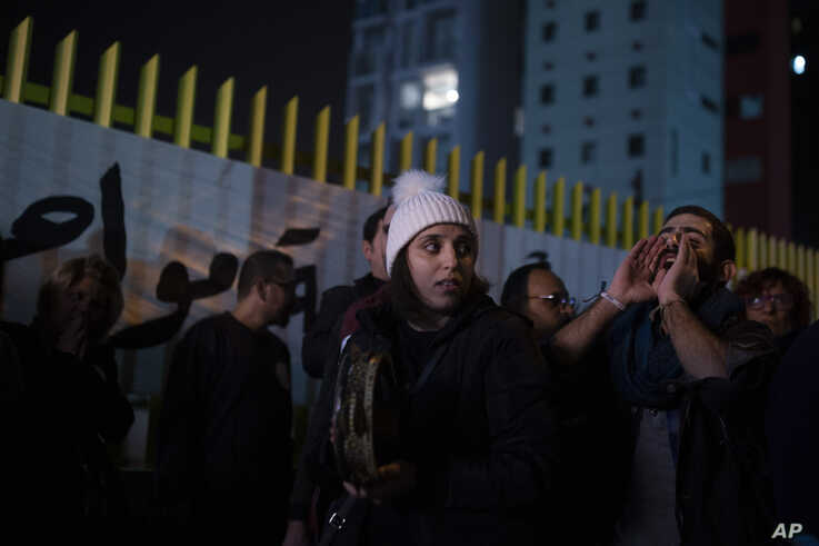 An anti-government protester, right, leads a chant as activists gather outside of the state-run electricity company in Beirut,…