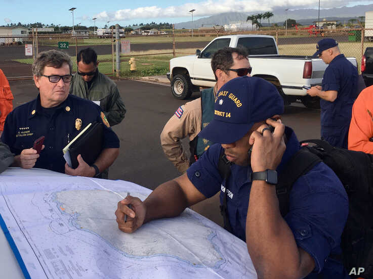 In this photo released by the U.S. Coast Guard, Coast Guard Incident Command Post responders look over a map of the Na Pali…