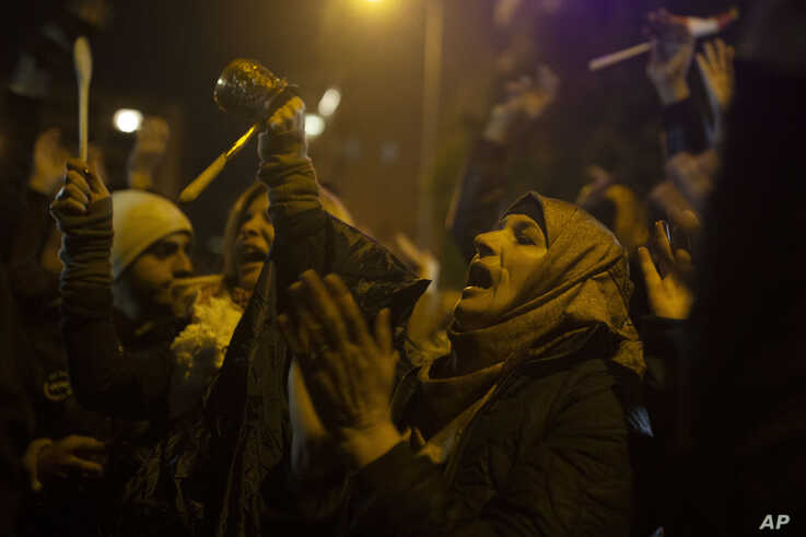 Anti-government protesters chant slogans outside of the residence of Hassan Diab, Lebanon's Prime Minister-designate on…
