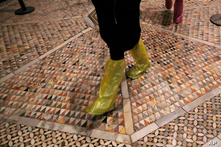 People walk on an interior mosaic floor of the St. Mark's Basilica in Venice, Italy, Tuesday, Dec. 17, 2019.  Still invisible…