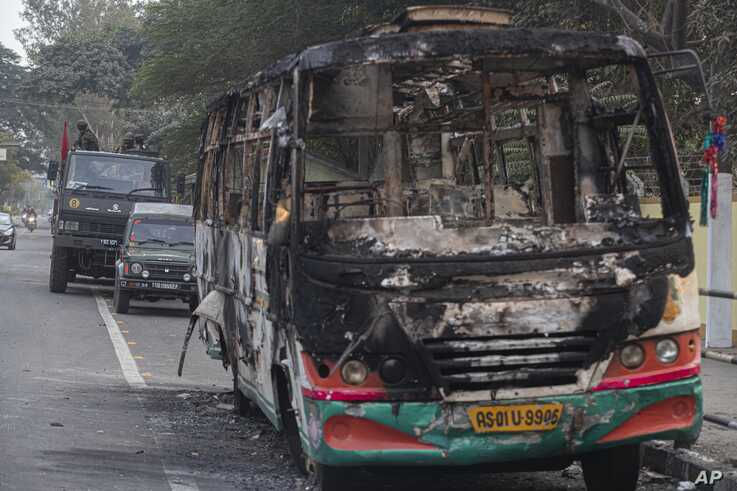 Indian army vehicles are parked behind a bus which was burnt by protesters during a protest against the Citizenship Amendment…