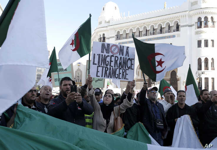 "An Algerian woman holds a banner reading ""No to foreign interference"" during a march against EU interference into Algeria's…"