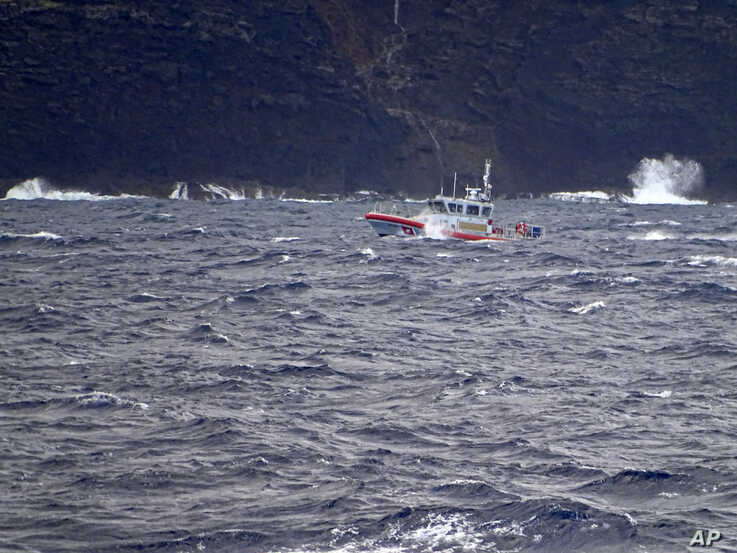 In this photo released by the U.S. Coast Guard, a coast guard vessel searches along the Na Pali Coast on the Hawaiian island of…