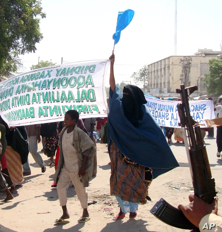 """Protesters carry banners which reads"""" Down with those who carried the killings"""" in Mogadishu, Somalia, Monday, Dec. 7, 2009. …"""