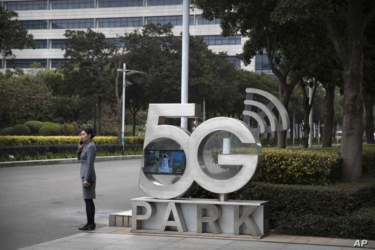 A Huawei employee talks on her cellphone as she stands next to a sign at Huawei's campus in Shenzhen in southern China's…
