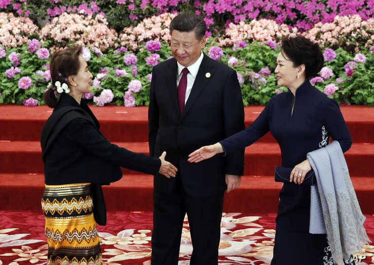Myanmar State Councellor Aung San Suu Kyi , left, arrives to attend a welcoming banquet for the Belt and Road Forum hosted by…