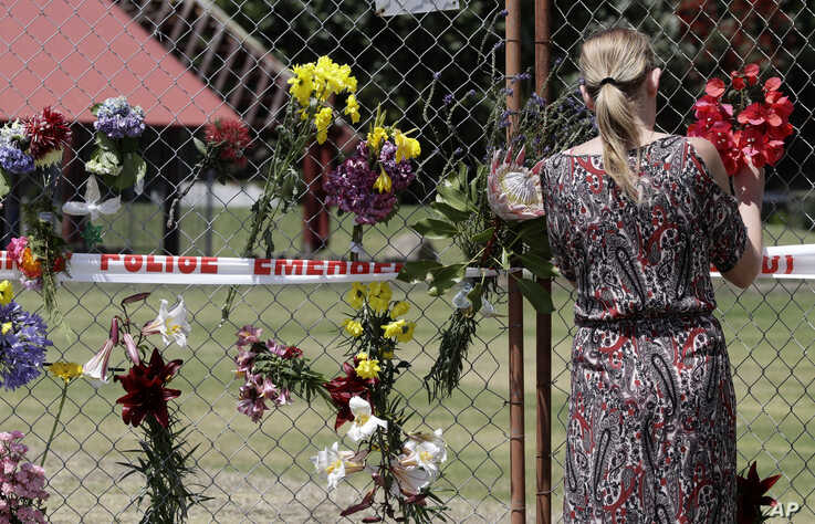 A woman places flowers on a fence at the waterfront in Whakatane, New Zealand, Wednesday, Dec. 11, 2019. Survivors of a…