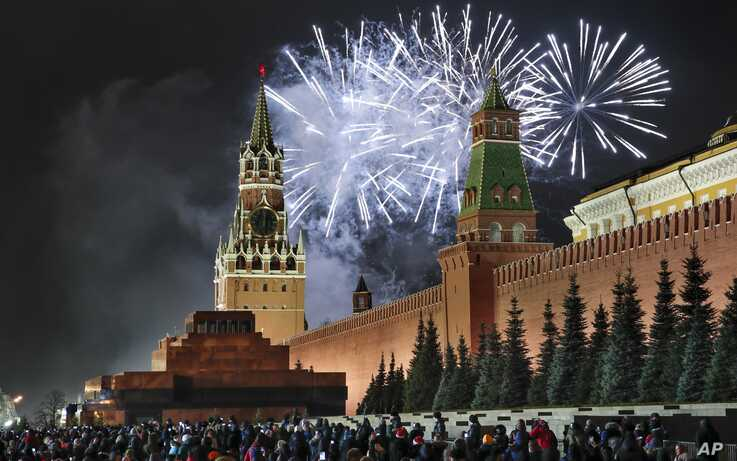 Fireworks explode over the Kremlin during New Year's celebrations in Red Square with the Spasskaya Tower, left, in the…