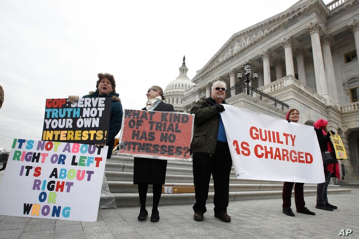 Protesters hold signs and sing outside the U.S. Capitol Friday Jan 31, 2020, in Washington, as Senators continue the…