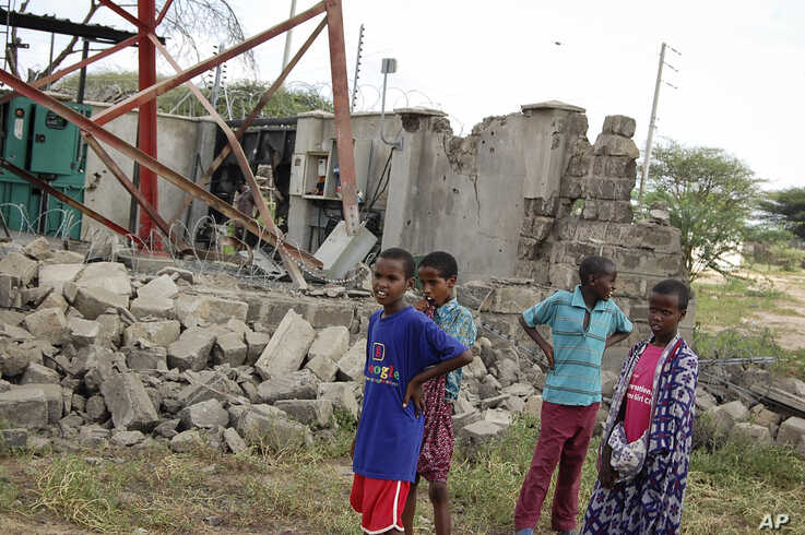 Children look at a damaged telecommunications mast after an attack by al-Shabab extremists in the settlement of Kamuthe in…