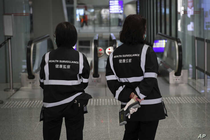 A health surveillance officer with temperature scanner waits for passengers at the Hong Kong International airport in Hong Kong…
