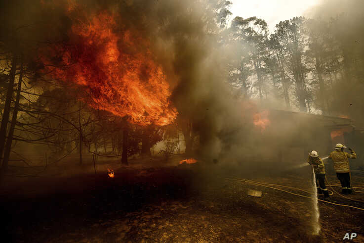 Firefighters battle the Morton Fire as it consumes a home near Bundanoon, New South Wales, Australia, Thursday, Jan. 23, 2020. …