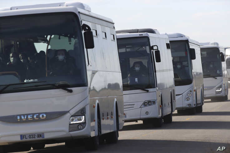 French passengers leave in buses a military air base, Friday Jan.31, 2020 in Istres, southern France after arriving by plane…