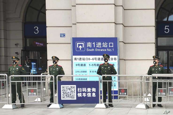 Paramilitary police stand guard at an entrance to the closed Hankou Railway Station in Wuhan in central China's Hubei Province,…
