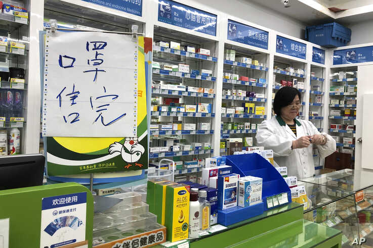 """Pharmacist Liu Zhuzhen stands near a sign reading """"face masks are sold out"""" at her pharmacy in Shanghai, Tuesday, Jan. 21, 2020…"""