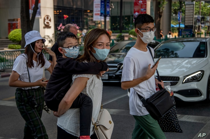 Chinese family wearing face masks walk in a pedestrian crossing in Bangkok, Thailand, Wednesday, Jan. 29, 2020. Tourism Council…