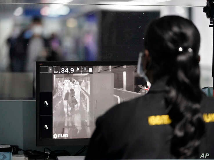 A health official watches travelers on a thermographic monitor at the Kuala Lumpur International Airport in Sepang, Malaysia,…