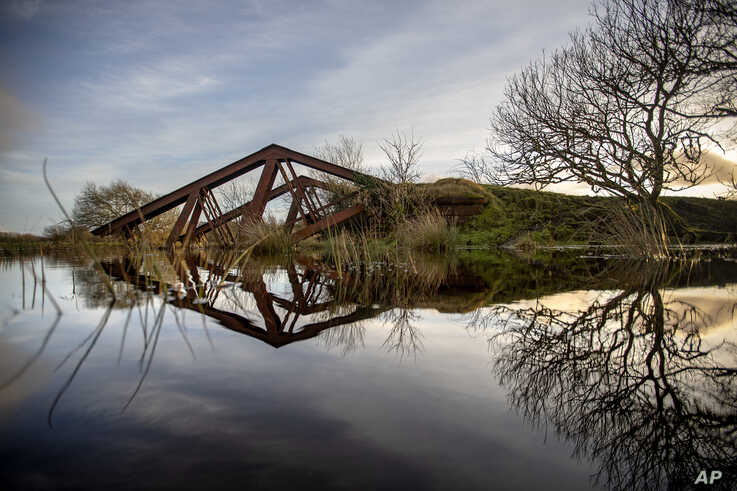 An old railway bridge blown up by the British Army in the 1970s is partially submerged in the Belcoo River that separates…
