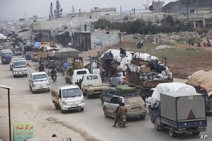 Syrian flee the advance of the government forces in the province of Idlib, Syria, towards the Turkish border, Wednesday, Jan…