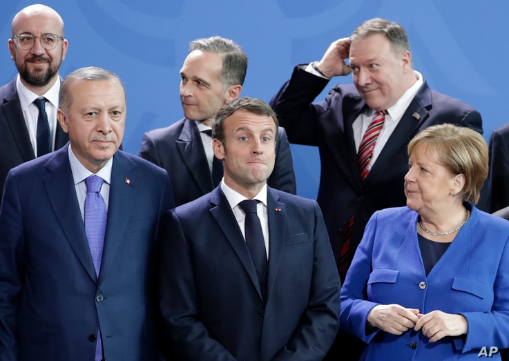 German Chancellor Angela Merkel, front right, speaks with French President Emmanuel Macron, front center, during a group photo…