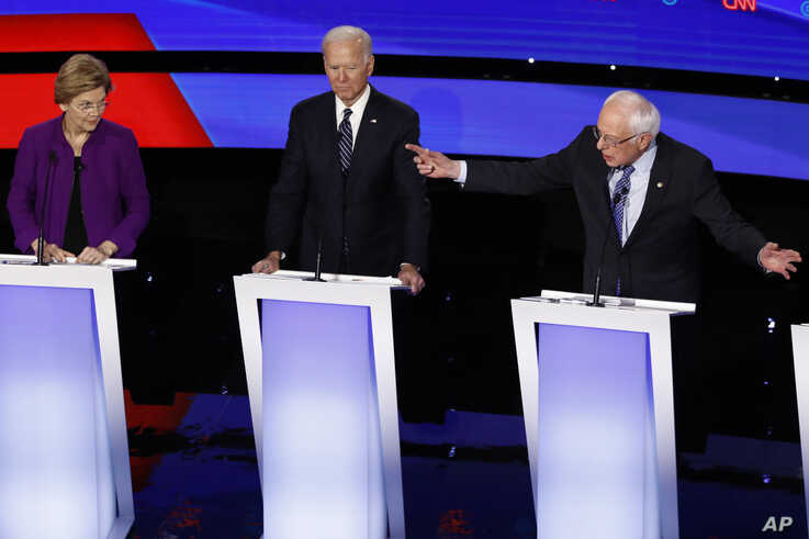 Democratic presidential candidate Sen. Bernie Sanders, I-Vt., right, speaks to Sen. Elizabeth Warren, D-Mass., left, as former…