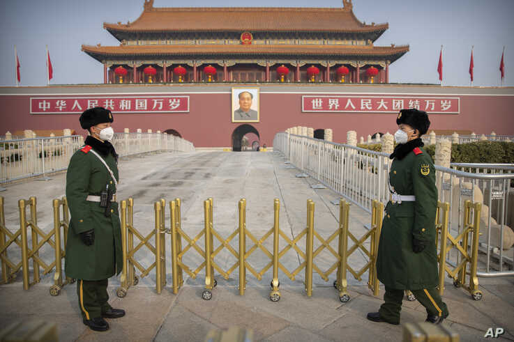 Paramilitary police wear face masks as they stand guard at Tiananmen Gate adjacent to Tiananmen Square in Beijing, Monday, Jan…