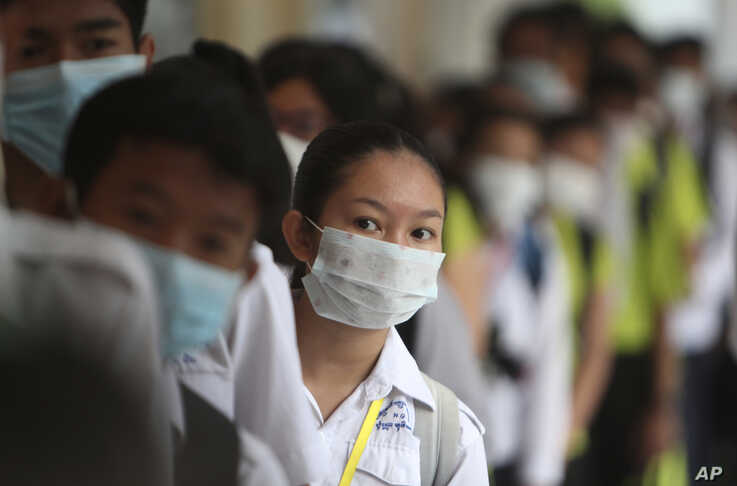 Students line up to sanitize their hands to avoid the contact of coronavirus before their morning class at a hight school in…