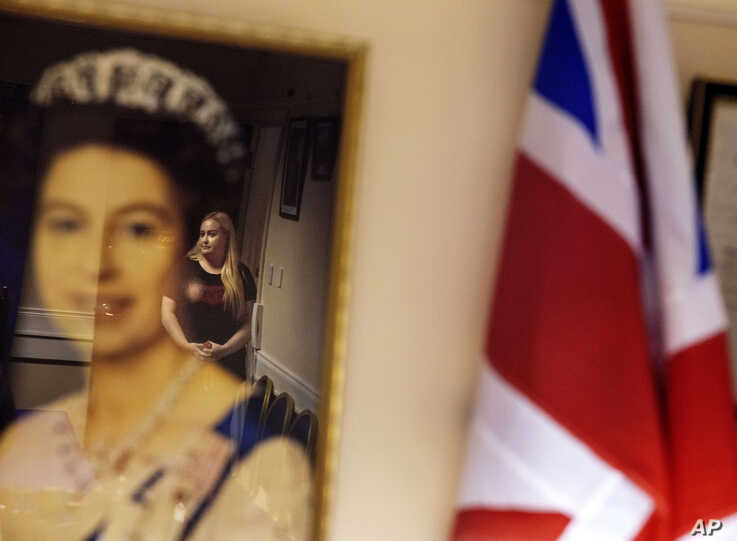 Lisa Partridge, 28, who grew up with the Protestant Loyal Orange Institution, is reflected in a portrait of Queen Elizabeth II…