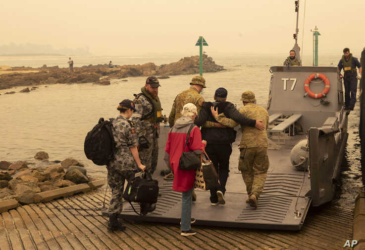 In this photo released by the Australian Department of Defense, evacuees board landing craft to be ferried out to the navy's…