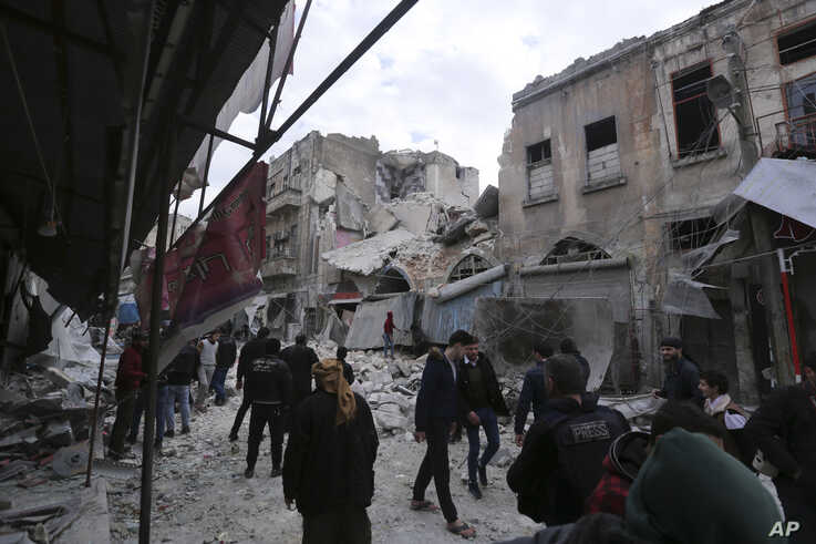 People walk past destruction by the government airstrikes in the town of Ariha, in Idlib province, Syria, Wednesday, Jan. 15,…