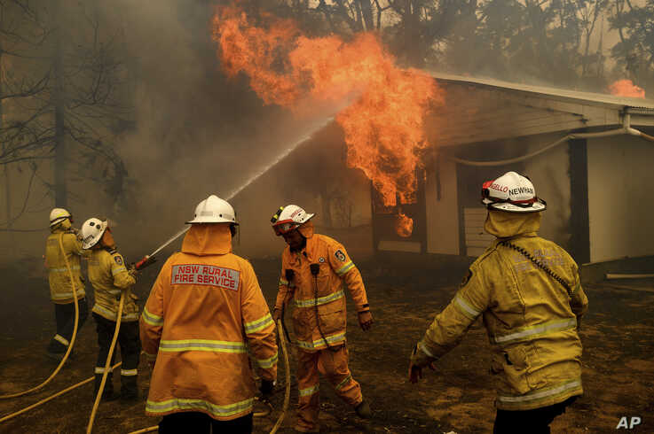 Firefighters battle the Morton Fire as it burns a home near Bundanoon, New South Wales, Australia, on Thursday, Jan. 23, 2020. …