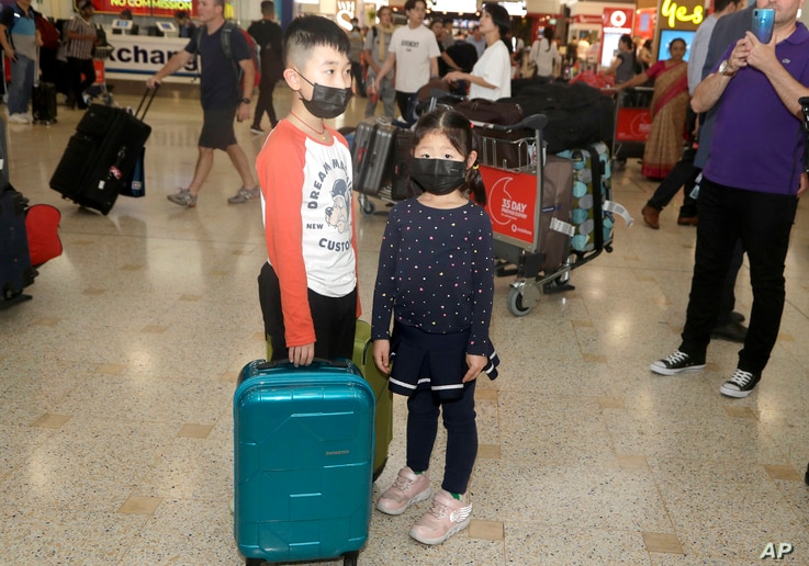 Children, wearing face masks, wait for their mother after arriving in Sydney Thursday, Jan. 23, 2020, from a flight from Wuhan,…
