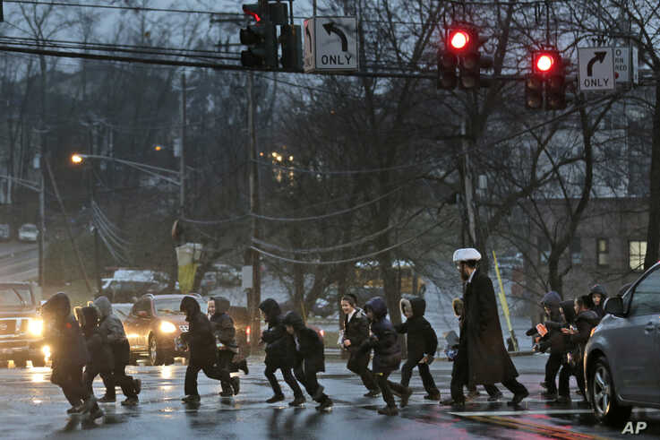 In this Monday, Dec. 30, 2019, photo, a group of orthodox Jewish children cross the street in Monsey, N.Y. With the rapid…