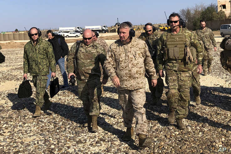 Gen. Frank McKenzie, center front, the top U.S. commander for the Middle East, walks as he visits a military outpost in Syria,…