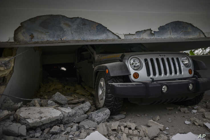 A car is crushed under a home that collapsed after the previous day's magnitude 6.4 earthquake in Yauco, Puerto Rico, Wednesday…