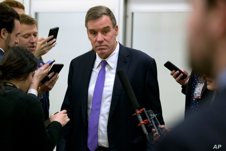 Sen. Mark Warner, D-Va., talks to reporters as he walks to attend the impeachment trial of President Donald Trump on charges of...