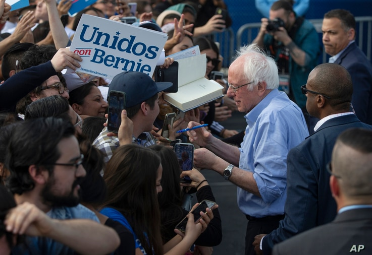 Democratic presidential candidate Sen. Bernie Sanders, I-Vt., signs autographs to Latino supporters at a campaign event at…