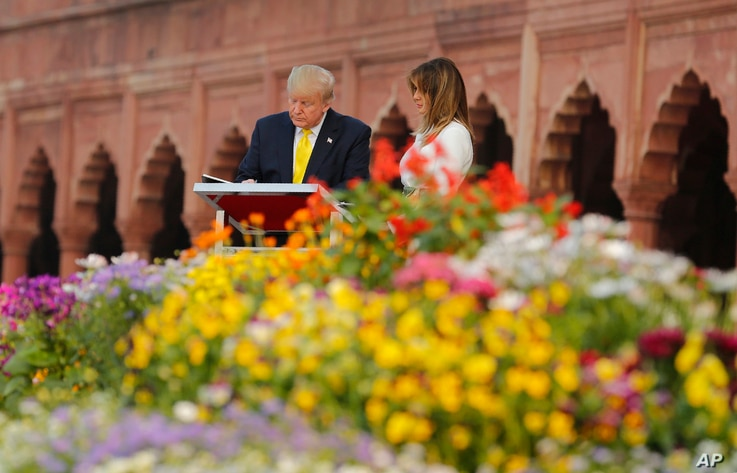 U.S. President Donald Trump signs visitors book as first lady Melania Trump watches during their visit to the Taj Mahal, the…