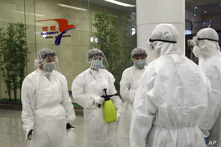State Commission of Quality Management staff in protective gear and disinfectant prepare to check the health of travelers…
