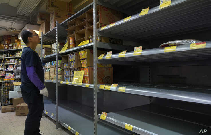 A worker checks empty shelf of rice at a supermarket in Hong Kong, Thursday, Feb. 6, 2020. Ten more people were sickened with a…