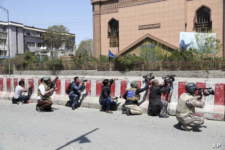 FILE- Afghan journalists work behind a barrier at the site of an attack on the Telecommunication Ministry in Kabul, April 20, 2019.