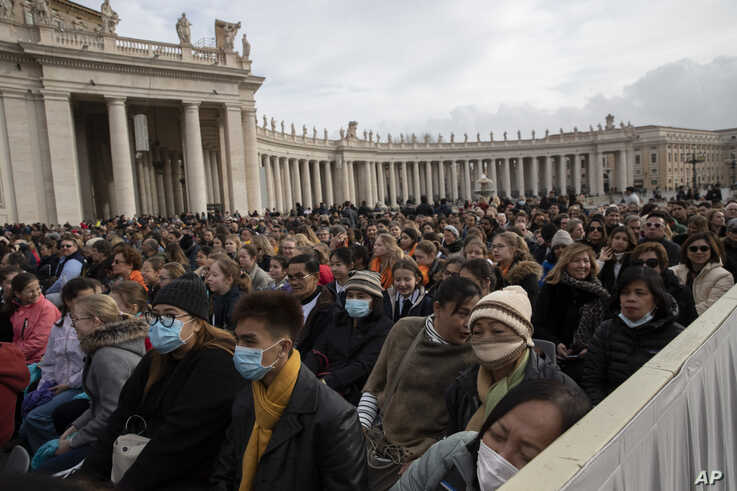 Faithful wear face masks as they wait for Pope Francis arrival in St. Peter's Square at the Vatican for his weekly general…