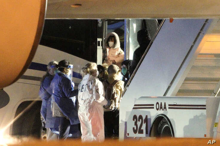 American evacuees from the coronavirus outbreak in China board a bus after arriving by flight to Eppley Airfield in Omaha, Nebrasaka, Feb. 7, 2020.