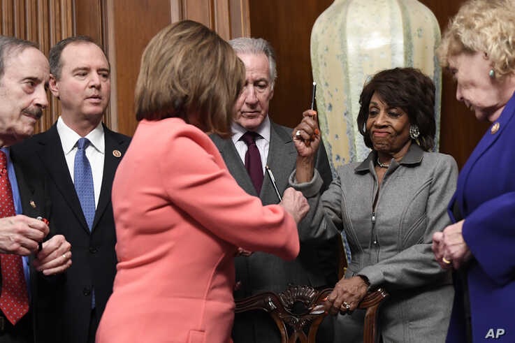 House Financial Services Committee Chairwoman Maxine Waters, D-Calif., second from right, reacts after getting a pen from House…