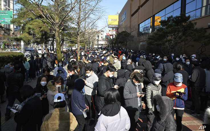 FILE - In this Feb. 24, 2020 file photo, People line up to buy face masks at a store in Daegu, South Korea. As fears of a…