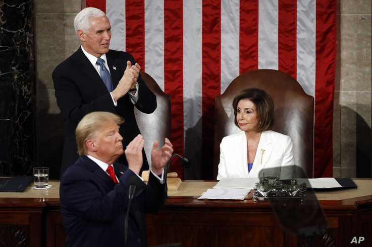 President Donald Trump and Vice President Mike Pence turns and applaud as he delivers his State of the Union address to a joint…