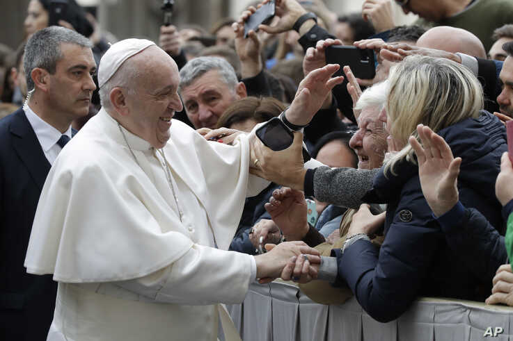 Pope Francis salutes faithful in St. Peter's Square at the Vatican before leaving after his weekly general audience, Wednesday,…