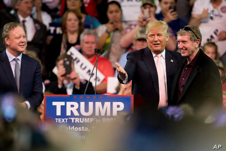 Republican presidential candidate Donald Trump, accompanied by NASCAR Chairman and CEO Brian France, left, invites up former…