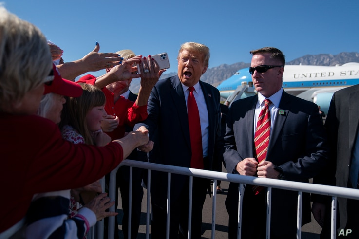 President Donald Trump greets supporters after arriving at Palm Springs International Airport in Palm Springs, Calif., en route…
