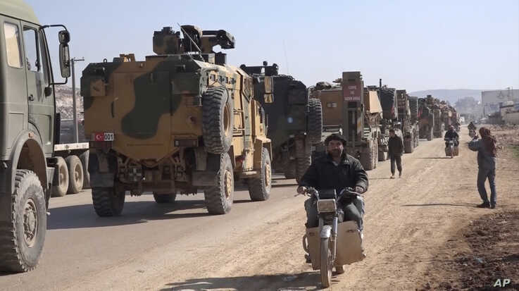 In this frame grab from video taken Feb. 2, 2020,  a large Turkish Armed Forces convoy is seen at the northern town of Sarmada, in Idlib province, Syria.